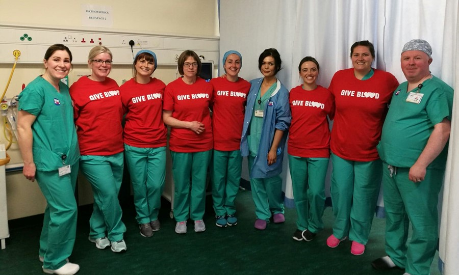 Group photo of the Edinburgh Royal Infirmary team dressed in scrubs and Give Blood t-shirts.
