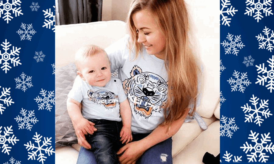 Rhiannon sits in living room with one year old Ollie on her knee. Both wear jeans and matching t-shirts.
