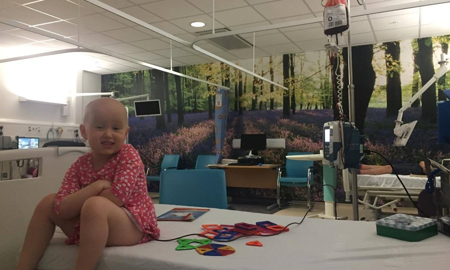 Emily, a small girl with no hair after chemotherapy, smiles at the camera while having a blood transfusion in hospital.