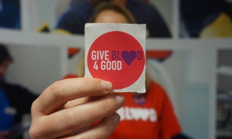 Young lady holding up a 'Give Blood 4 Good' sticker in front of her face
