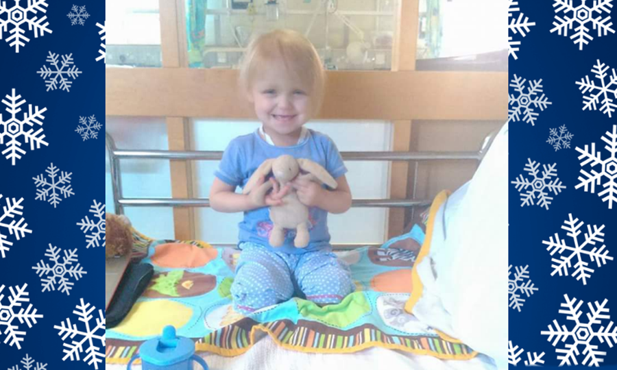 Amelia aged three, in hospital, cuddling a toy rabbit.