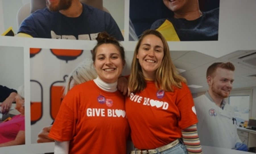 Martha and Hanna smiling wearing 'give blood' t-shirts and 'Give Blood 4 Good' stickers